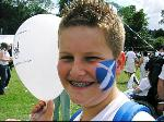 Boy with Scotland flag painted on his face and Make Poverty History balloon