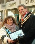 Barbara presents a plaque to the mayor