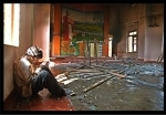 A tribal christian praying in a burnt down church