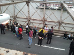 protesters in plastic cuffs awaiting transport off the bridge by bus