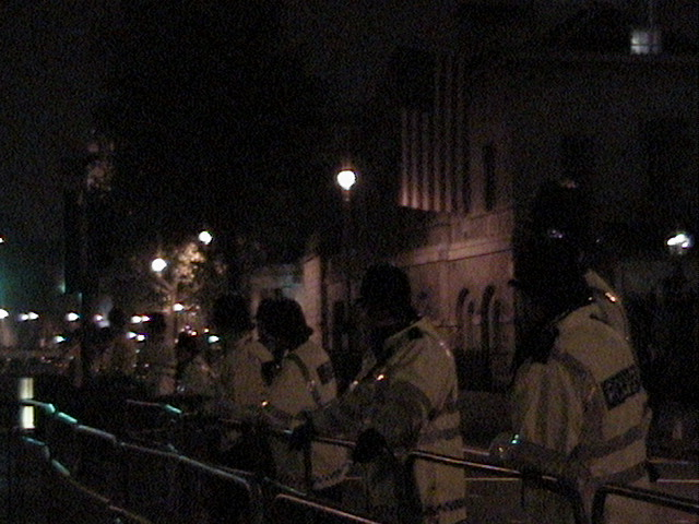 Police in front of American flag hanging from the Horse Guard