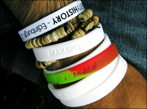 White Make Poverty wrist bands with a new Respect wrist band