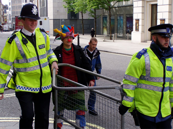 police need help moving crowd control barriers - luckily a clown assists