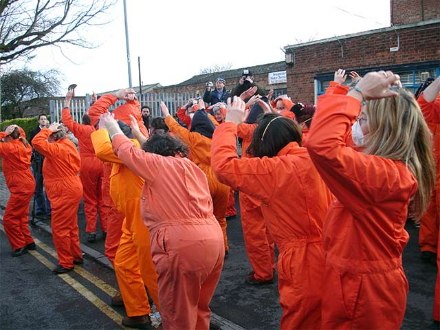 "and people in orange jump suits doing the ""shackle-shuffle"""