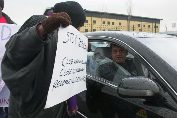 A demonstrator talks to a driver leaving the site