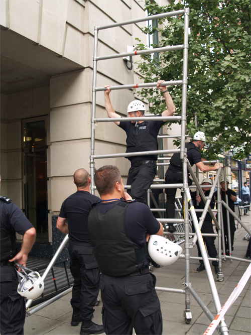 Police build a scaffold to get roof protesters
