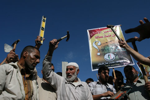 Palestinian workers, holding work tools, chant slogans as they demonstrate again