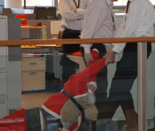 Suits drag santa in office bail out shocker