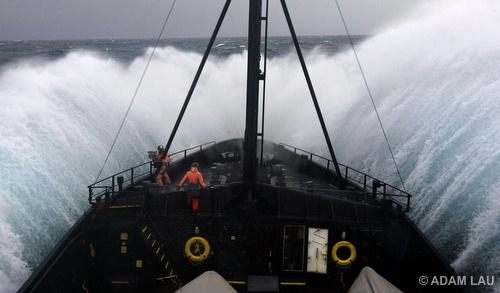 Crew bracing as ship plunges into the trough of massive waves in rough seas