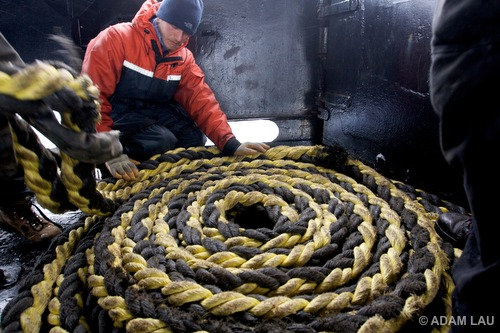 Crew member coils an prop fouler (used to disable ship's propellers)