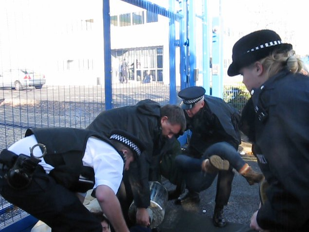 Police officers lift and move activists and concrete lock on.
