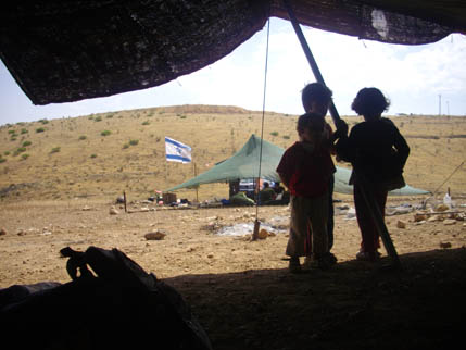 Palestinian children look out at the Maskiot settlers who are threatening them