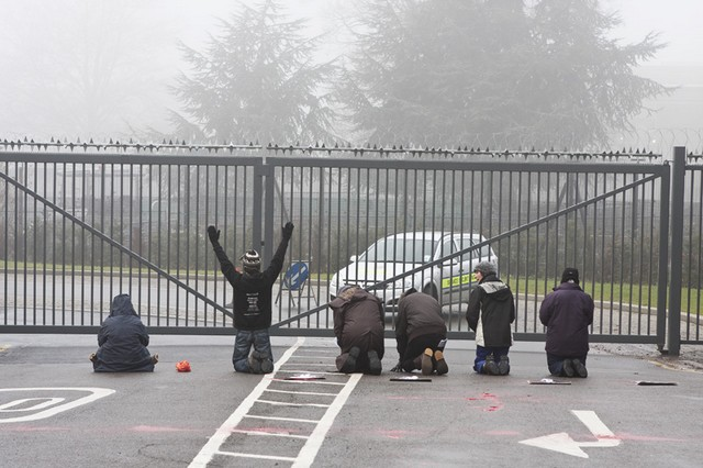 Activists kneel in prayer in front of the gates of Northwood