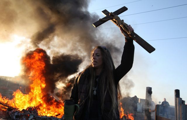 A woman raises her crucifix above the ruins of what was her home