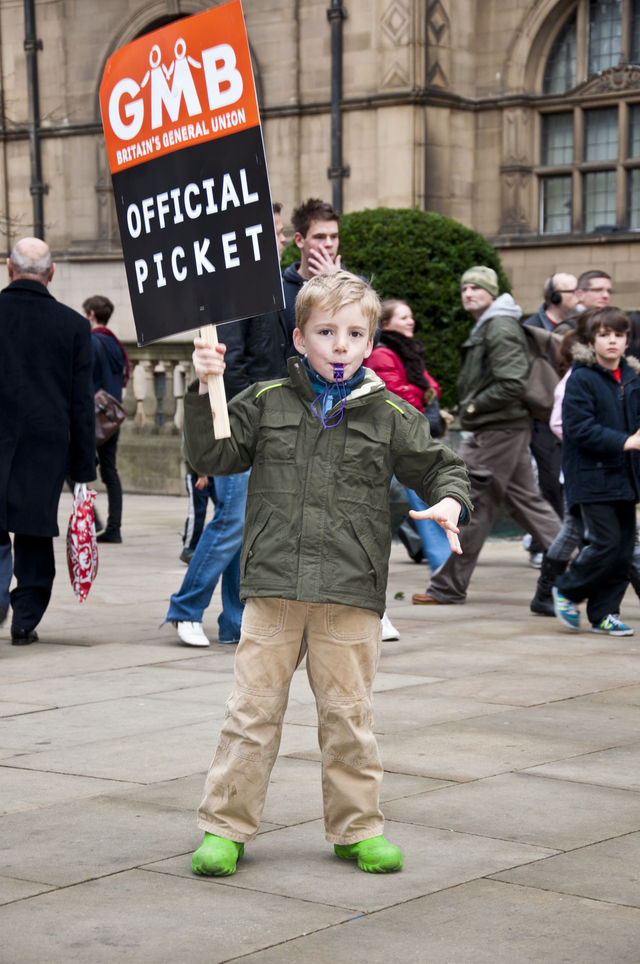 Children waving banners and blowing whistles in support of their parents.
