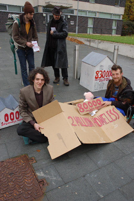 Tristan joins the protest outside (under the cardboard, left)