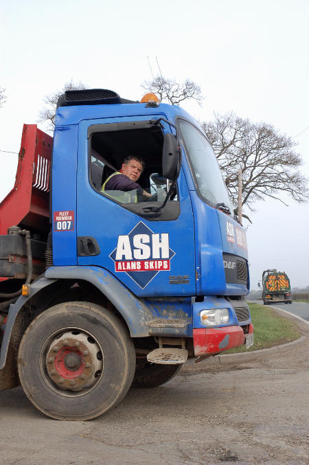 Alan's Skip Hire truck waiting to join main road