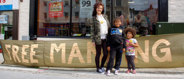 Kids with 'Free Manning' stickers pose for a photo (Castle Square)