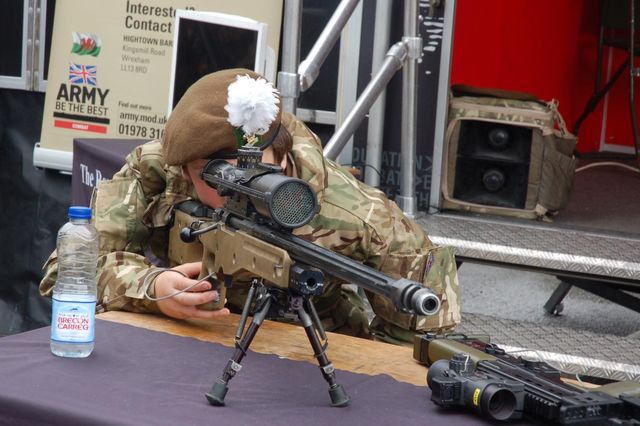 Young army cadet tries out a sniper rifle